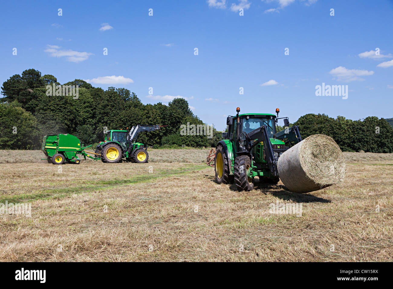 Tractor transporting baled hay with baling tractor behind, Castle Meadows, Abergavenny, Wales, UK - Stock Image