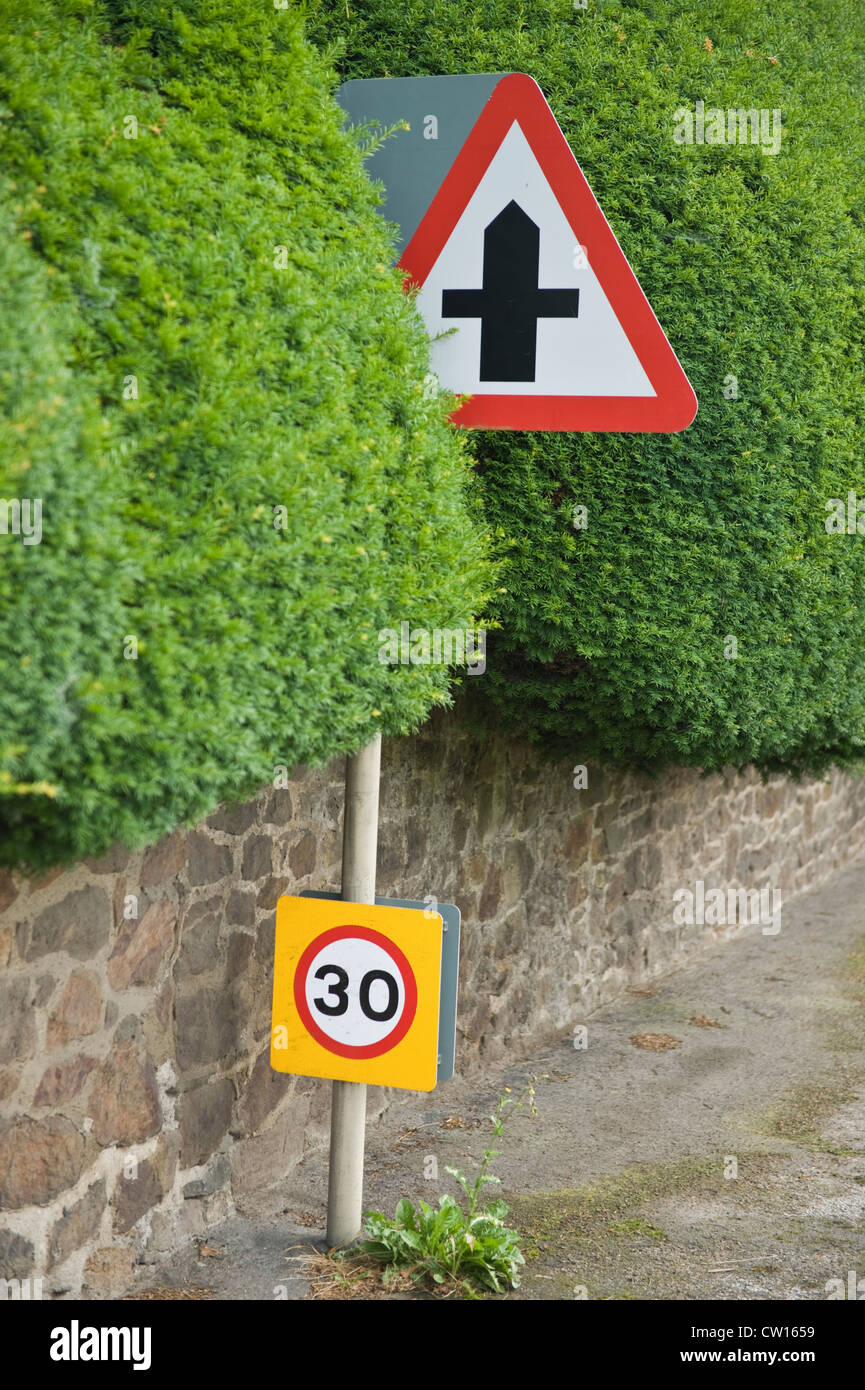 Crossroads and 30 miles per hour traffic sign in yew hedge at village of Brampton Bryan, Herefordshire, England, - Stock Image