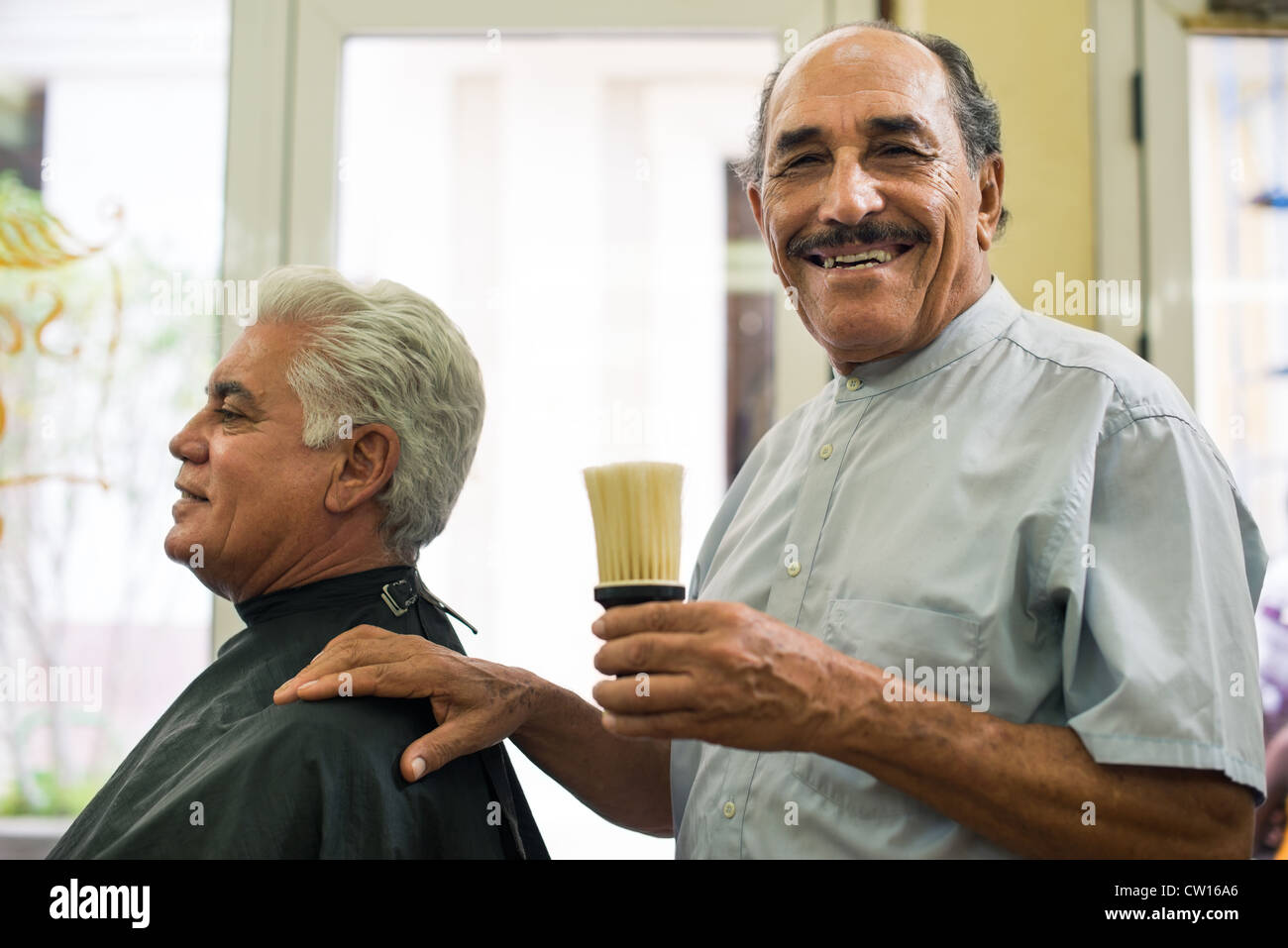 Old barber holding brush for talco and smiling to camera in old fashion barber shop - Stock Image