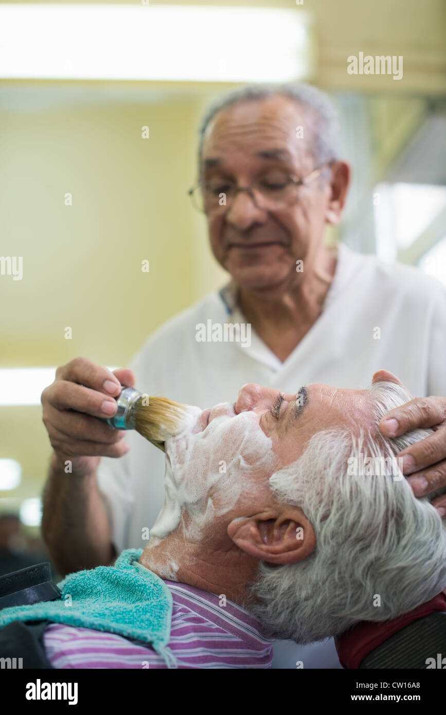 Elderly barber with shave brush applying cream to client in old style shop - Stock Image