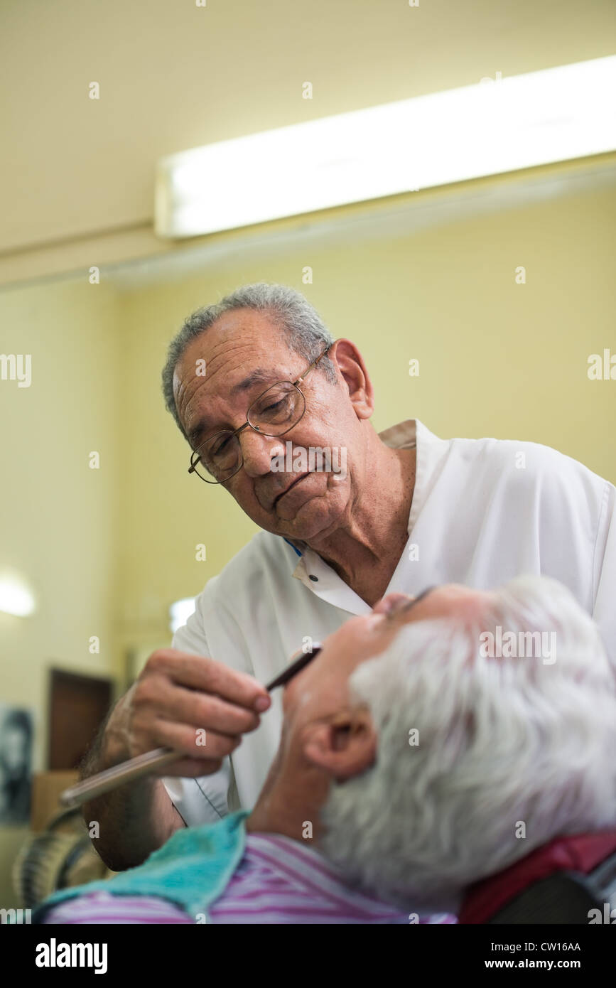 Senior man at work as barber shaving customer with razor in old fashion shop - Stock Image
