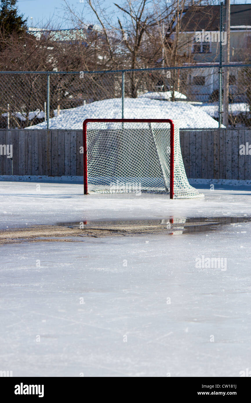 Ice hockey rink with hockey net on melting ice in the early spring