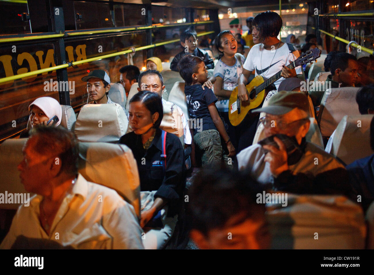 Buskers (ngamen) play music on a public bus at night in Surabaya, Indonesia. - Stock Image