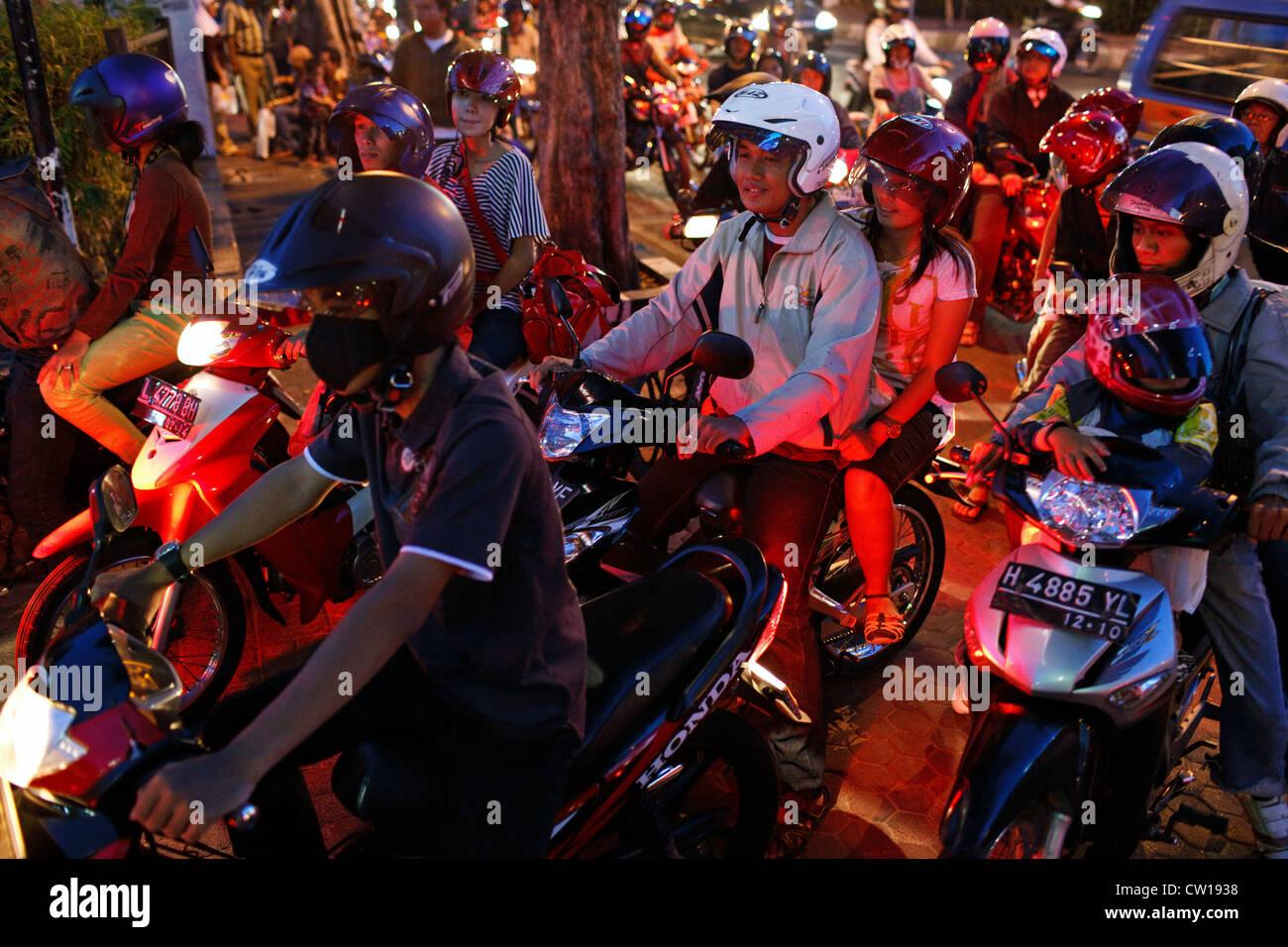 People on motorbikes at night in Surabaya, Indonesia. - Stock Image