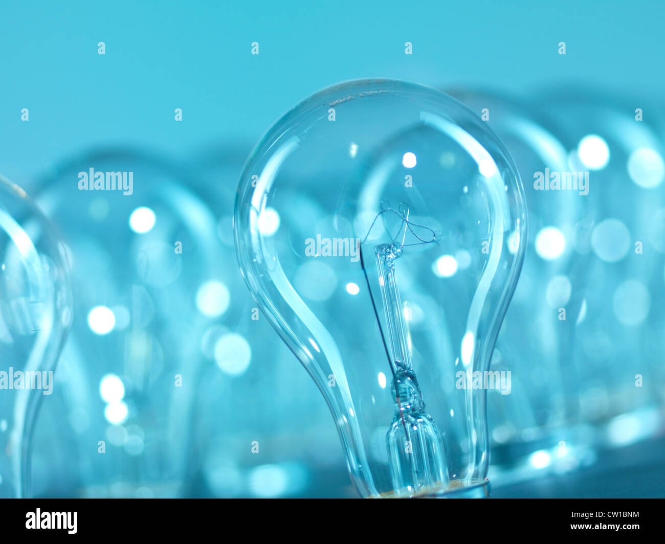Incandescent tungsten light bulbs abstract blue background - Stock Image