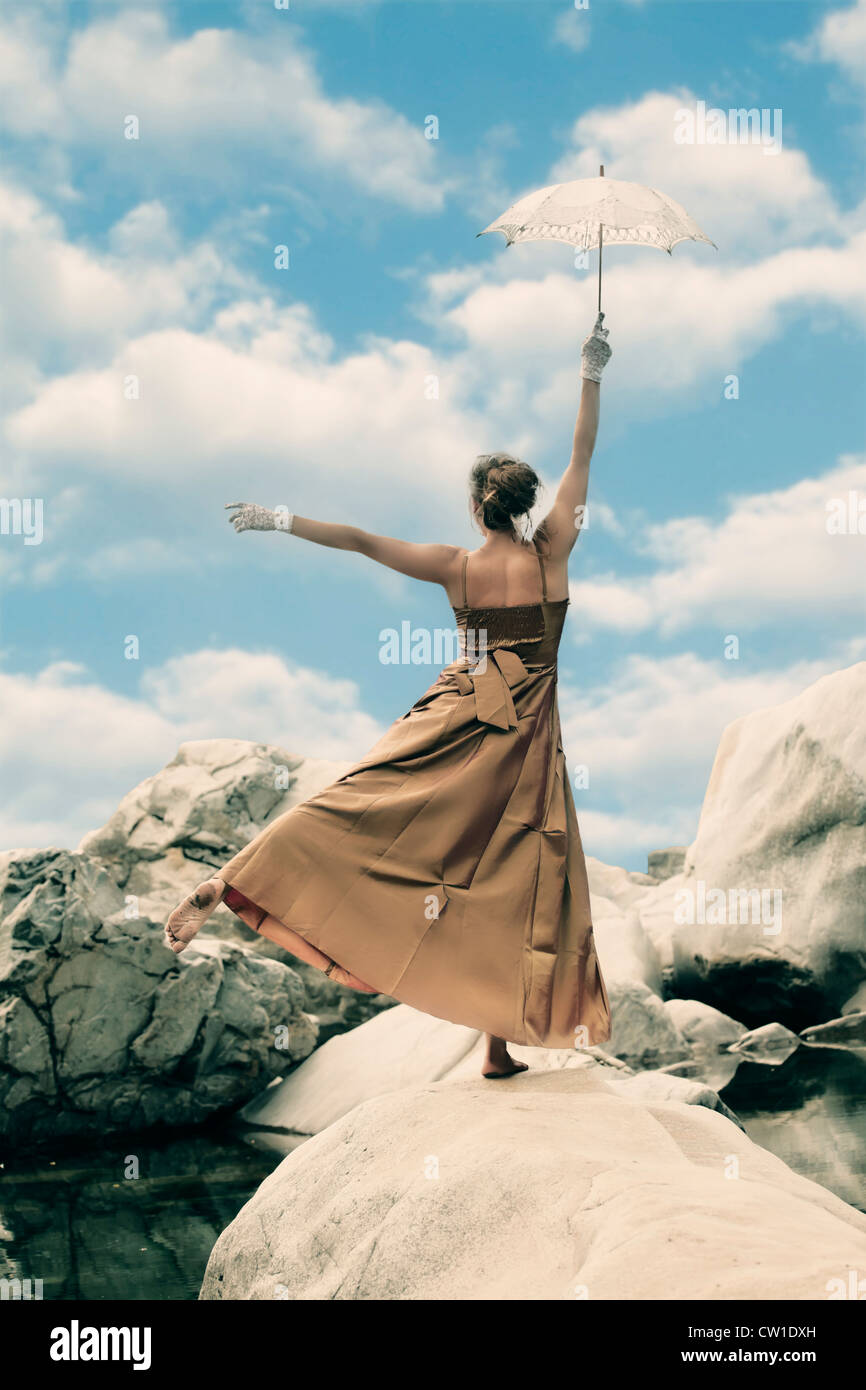 Woman stands on one leg on a rock and balances using an umbrella - Stock Image