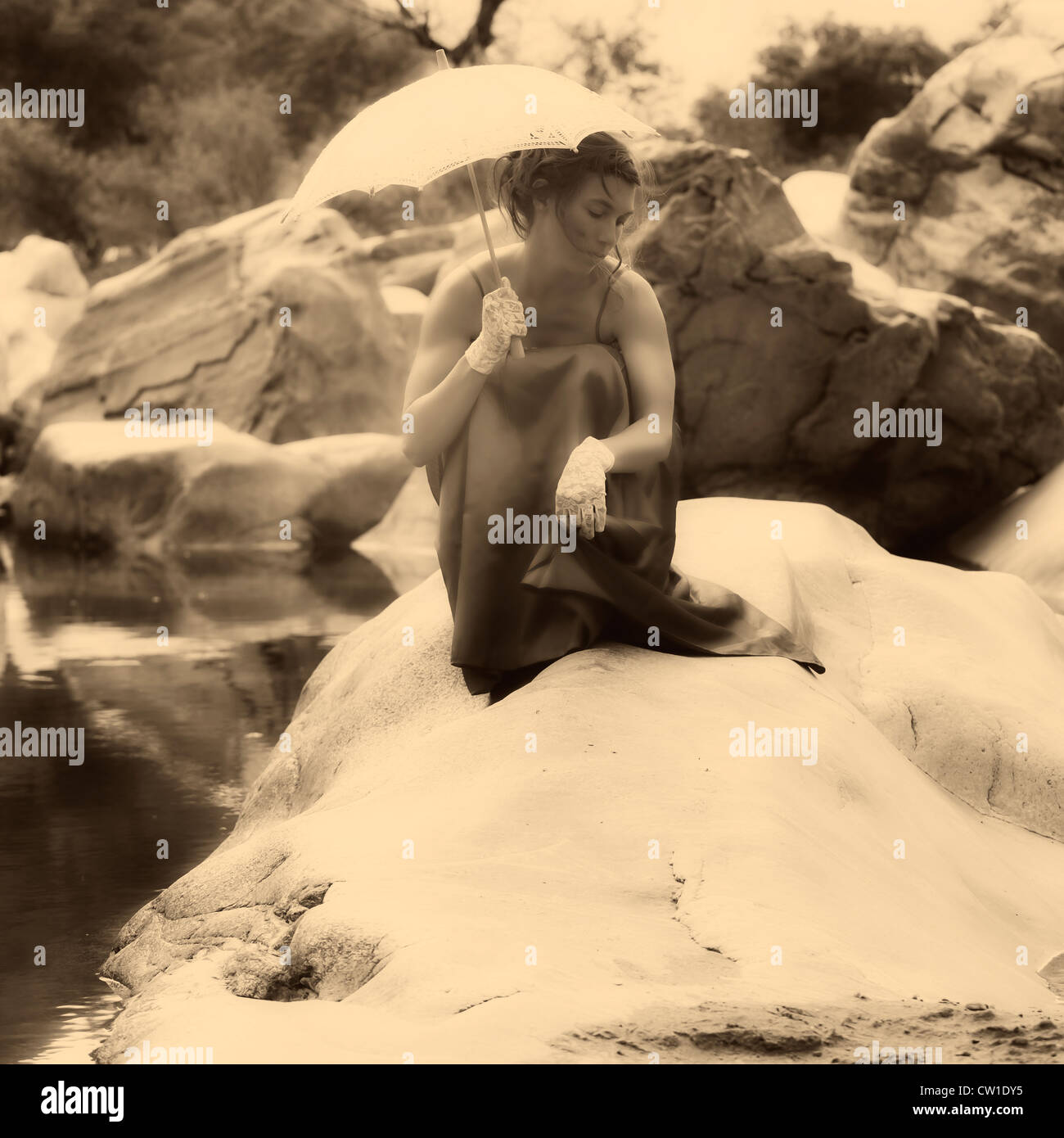 A young woman sitting on a rock in the water with a parasol - Stock Image
