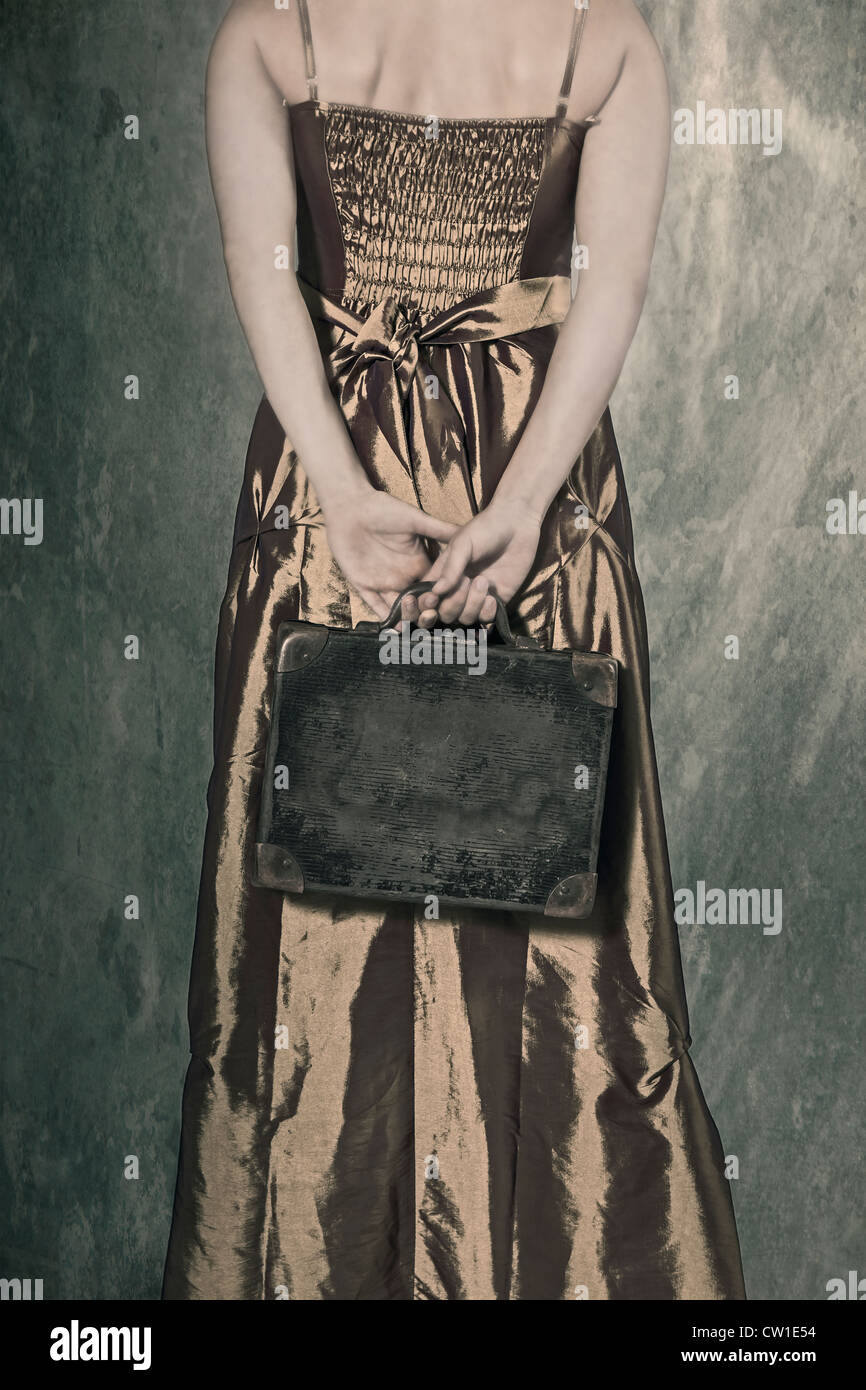 a woman in a period dress holding a small, old suitcase behind her back - Stock Image