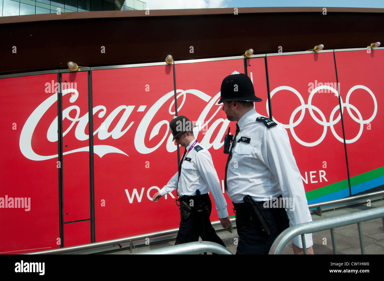 Westfield Shopping Centre, Stratford, entrance to the Olympic Park. Two policeman walk in front of an advert for Stock Photo