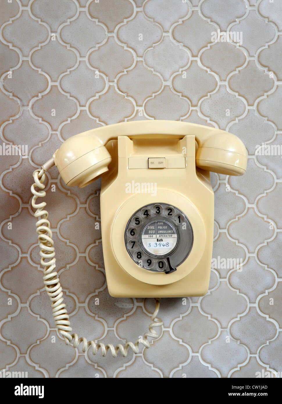 A classic wall mounted bakelite telephone in a 1970's style house which was featured in a 1975 magazine makeover - Stock Image