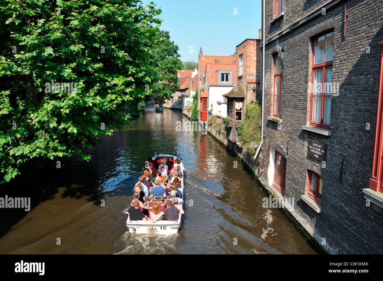 On a hot day in summer, a pleasure boat full of tourists slowly making its way along a Bruges canal. Belgium, Europe. - Stock Image