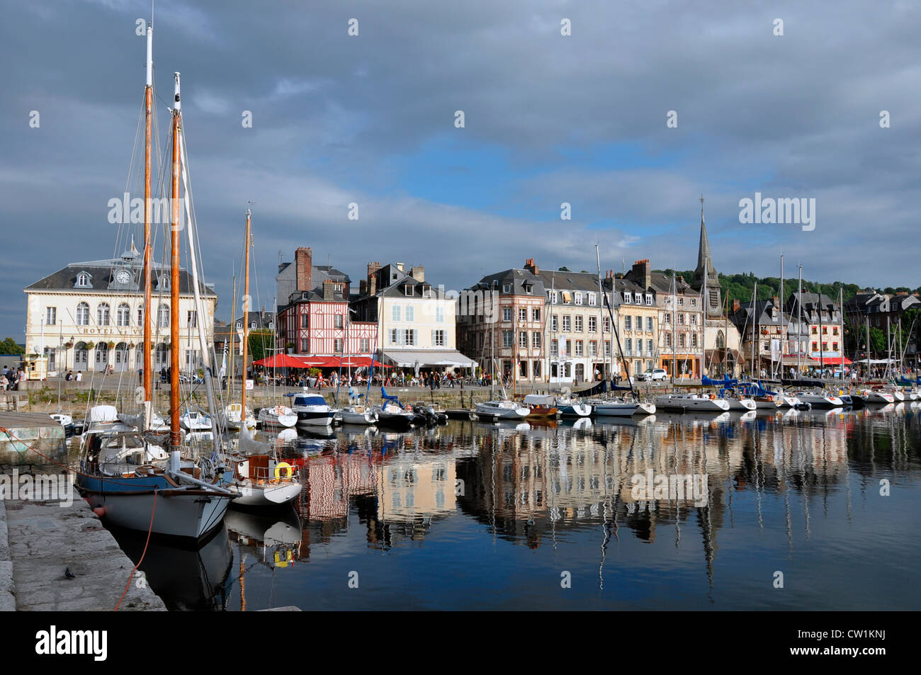 Late afternoon sunshine on picturesque Honfleur harbour, with a mirror image reflection in the still water of the - Stock Image