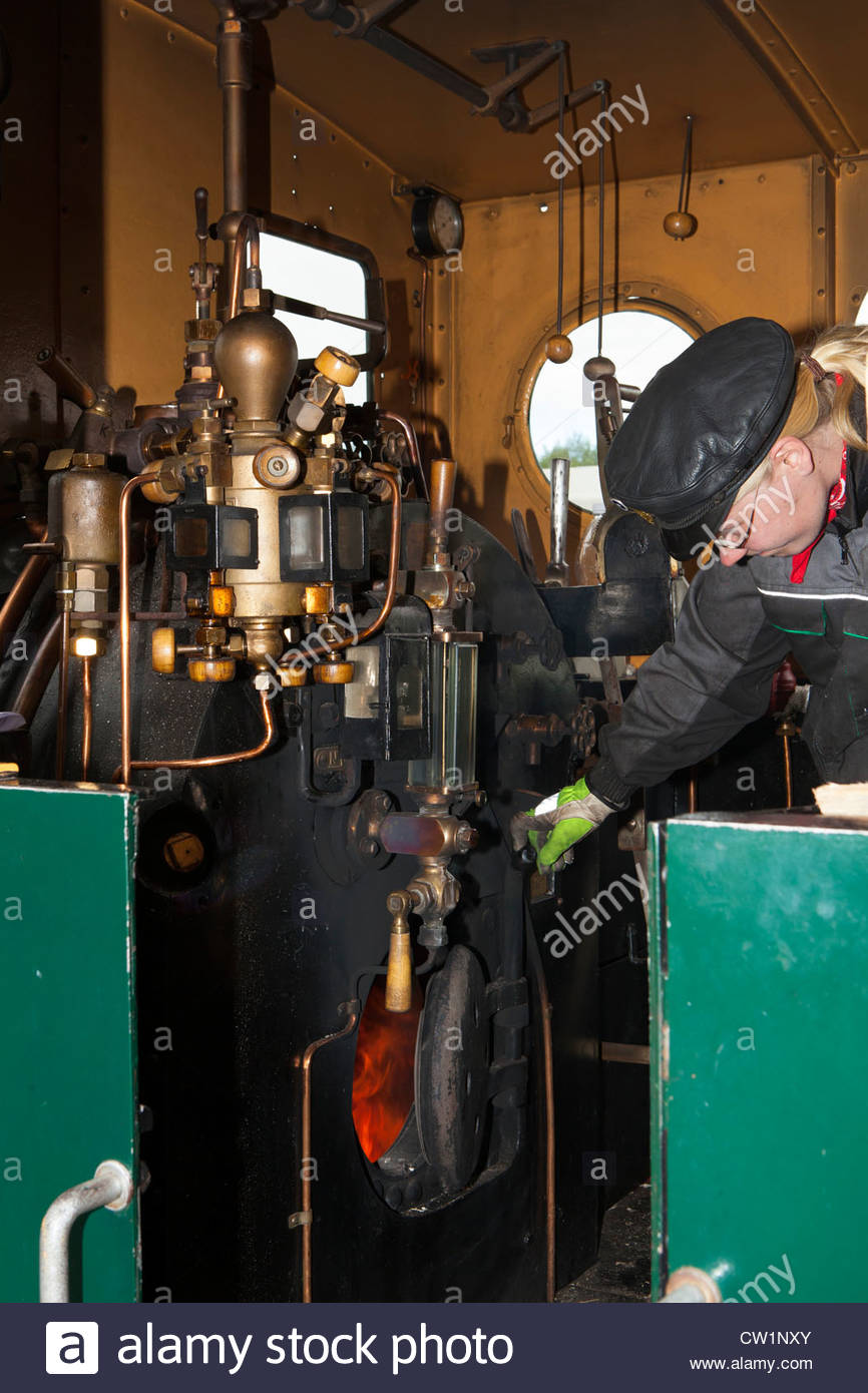 A female steam locomotive engineer checks the fire in her locomotives boiler. The engine is a Vk4 -class switcher. - Stock Image