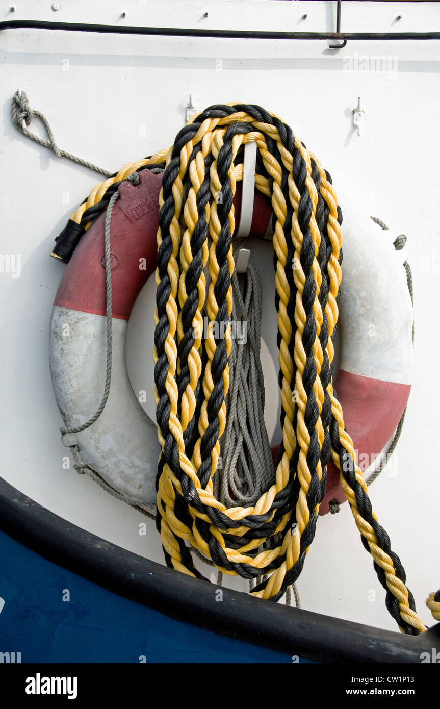 Coiled yellow and black rope hanging from hock in front of lifebuoy on boat - Stock Image