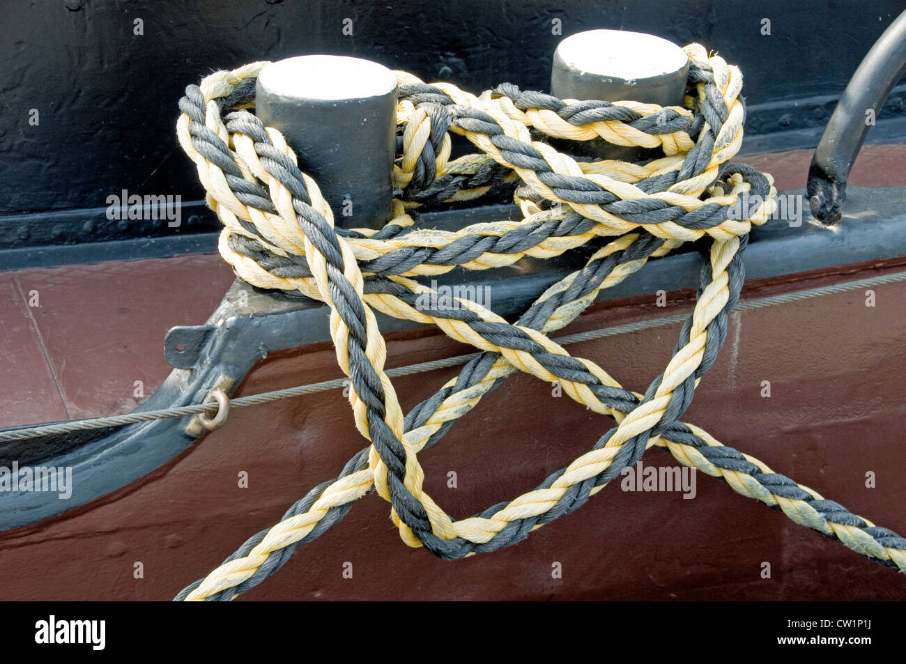 Black and yellow rope tied round mooring bollards on board boat - Stock Image