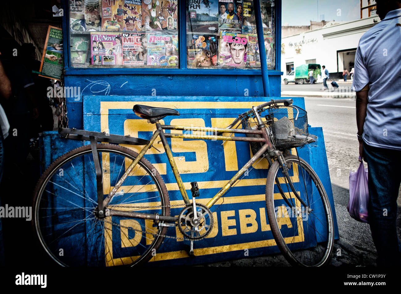 Bicycle leaning against a newsstand in Puebla, Mexico - Stock Image