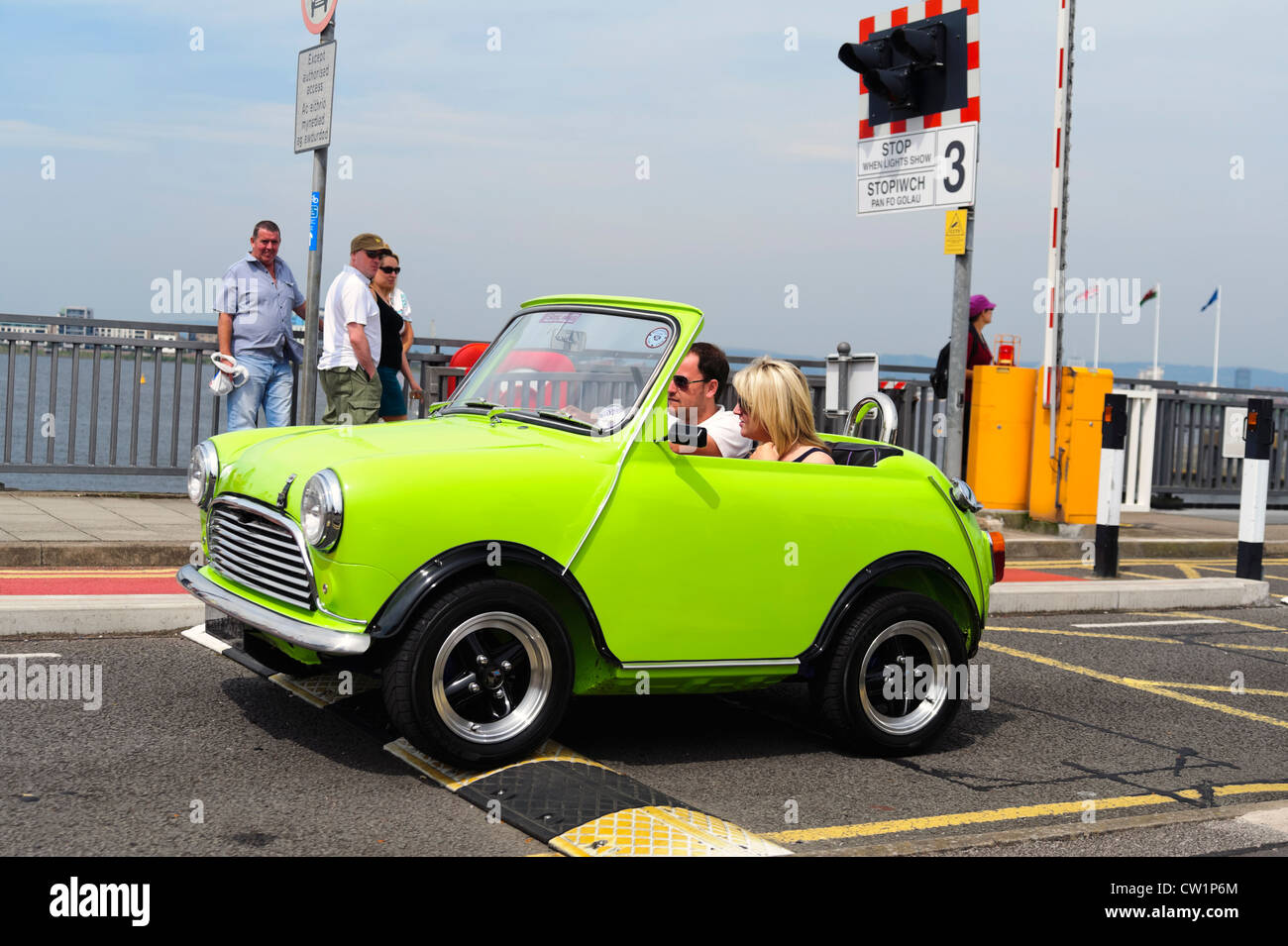 Classic mini car driving over a sleeping policeman speed bump on the Cardiff Bay Barrage, South Wales, UK. - Stock Image