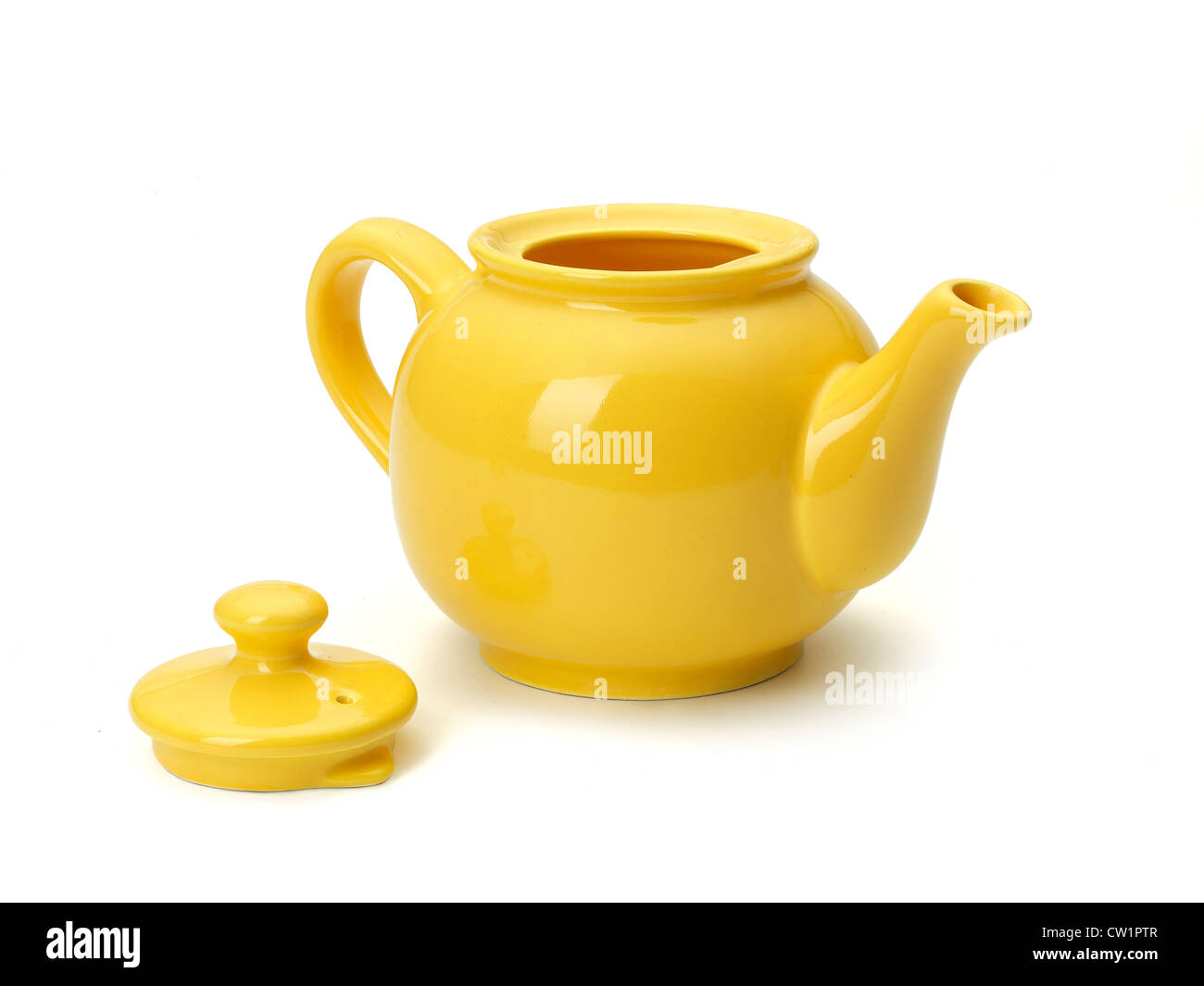 yellow tea pot on white background - Stock Image