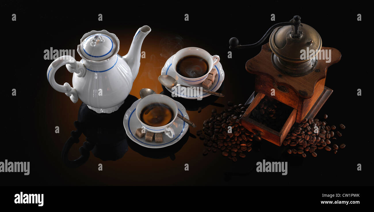 coffee set with coffee mill on reflective table - Stock Image