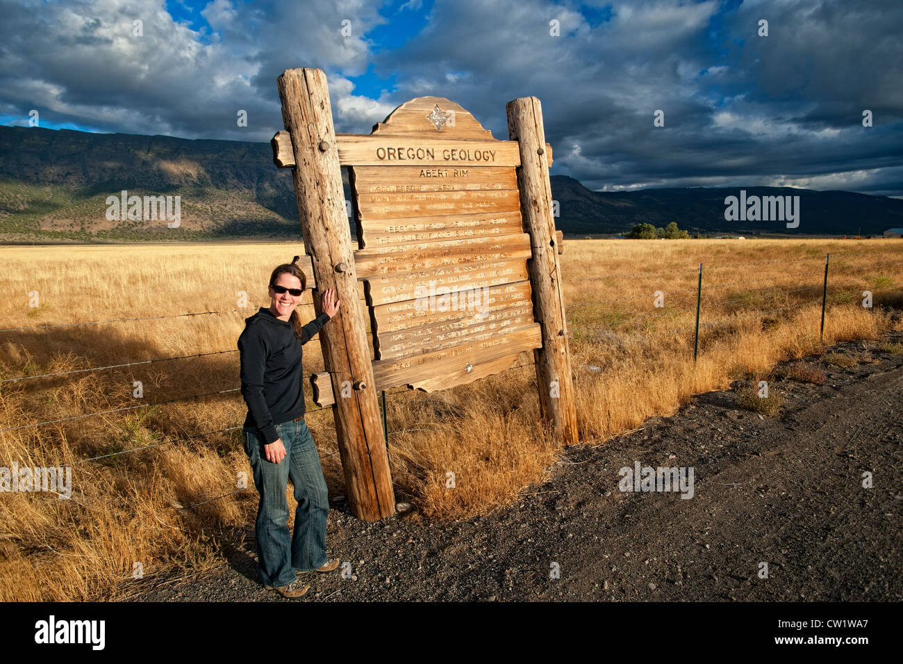 Woman standing at Oregon Geology roadside information sign which describes a geological fault line called Abert - Stock Image