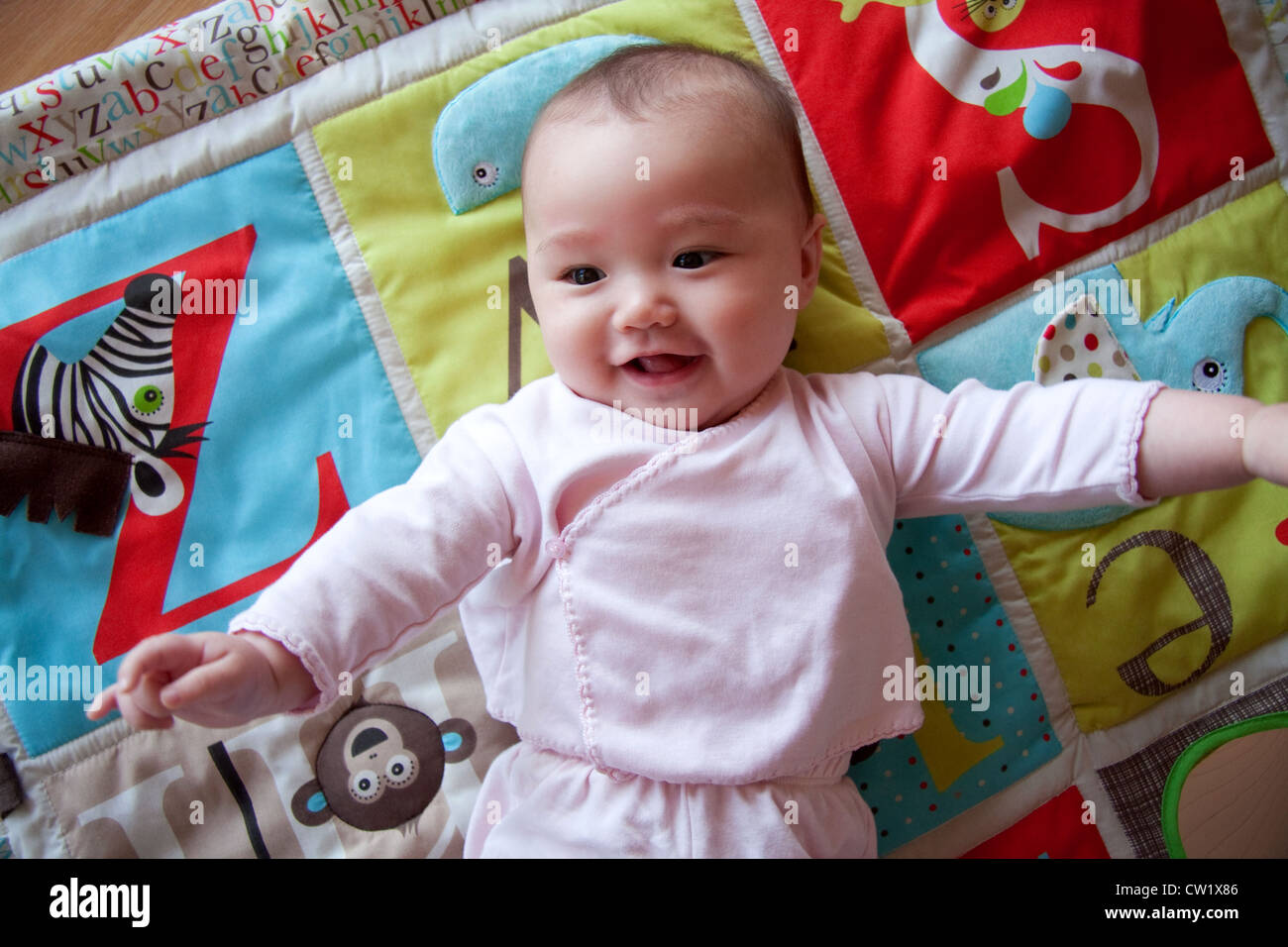 Happy baby on colorful playmat Stock Photo