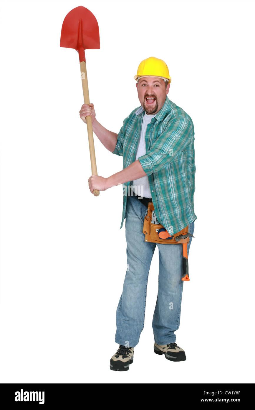 A delirious tradesman holding up a spade - Stock Image