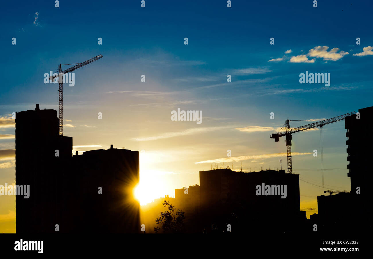 Industrial construction cranes and building silhouettes over sun at sunrise - Stock Image