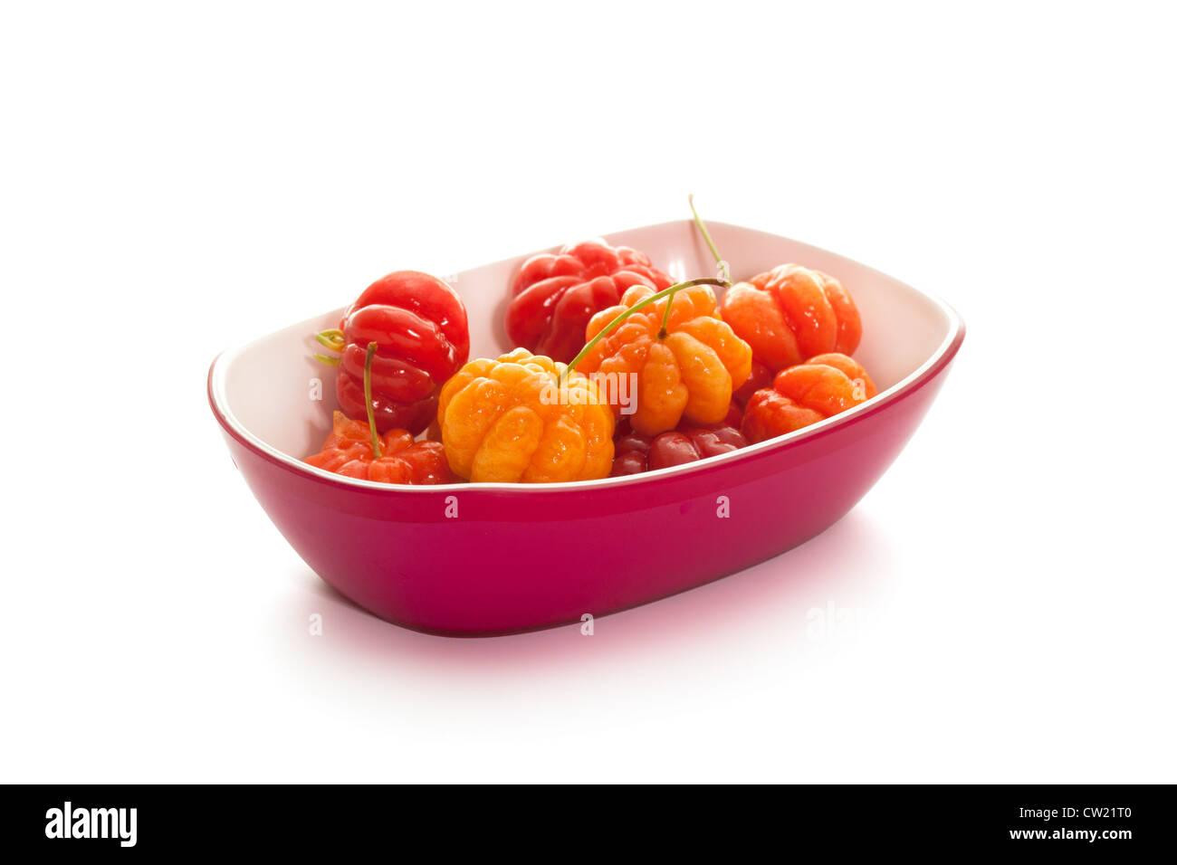 star gooseberry in magenta bowl on white background - Stock Image