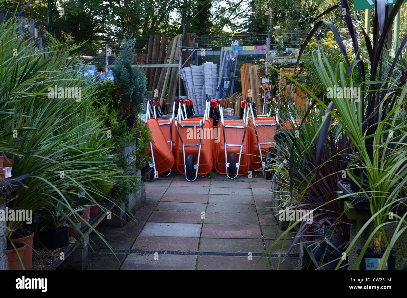 Stack of orange wheelbarrows in garden centre and row of plants - Stock Image