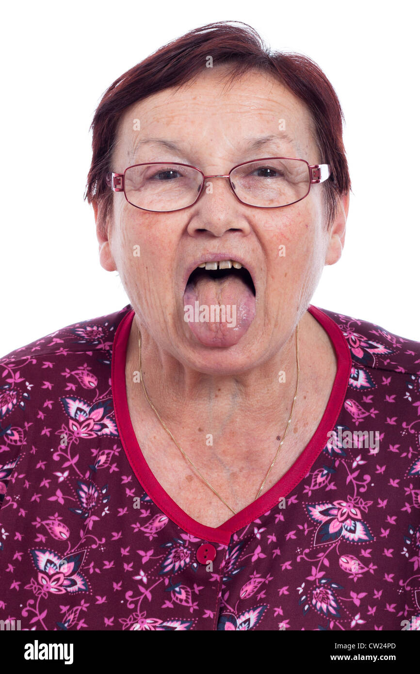Funny senior woman sticking out tongue, isolated on white background. - Stock Image