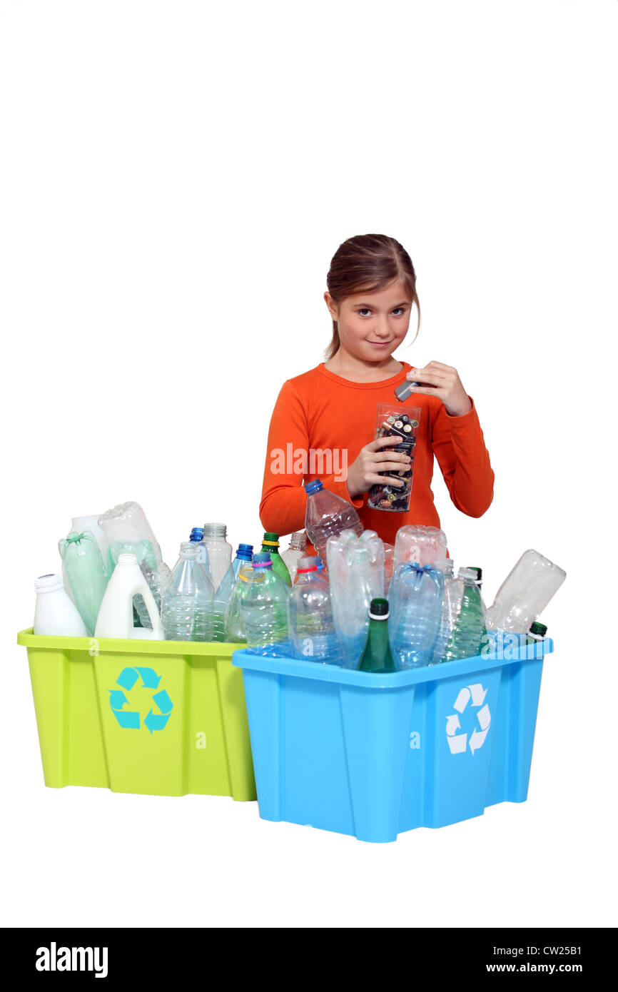 Young girl recycling plastic bottles and batteries - Stock Image