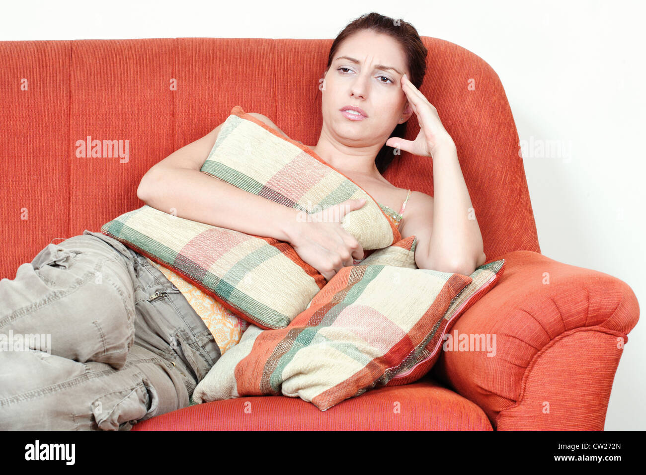Young woman on sofa having headache pain Stock Photo