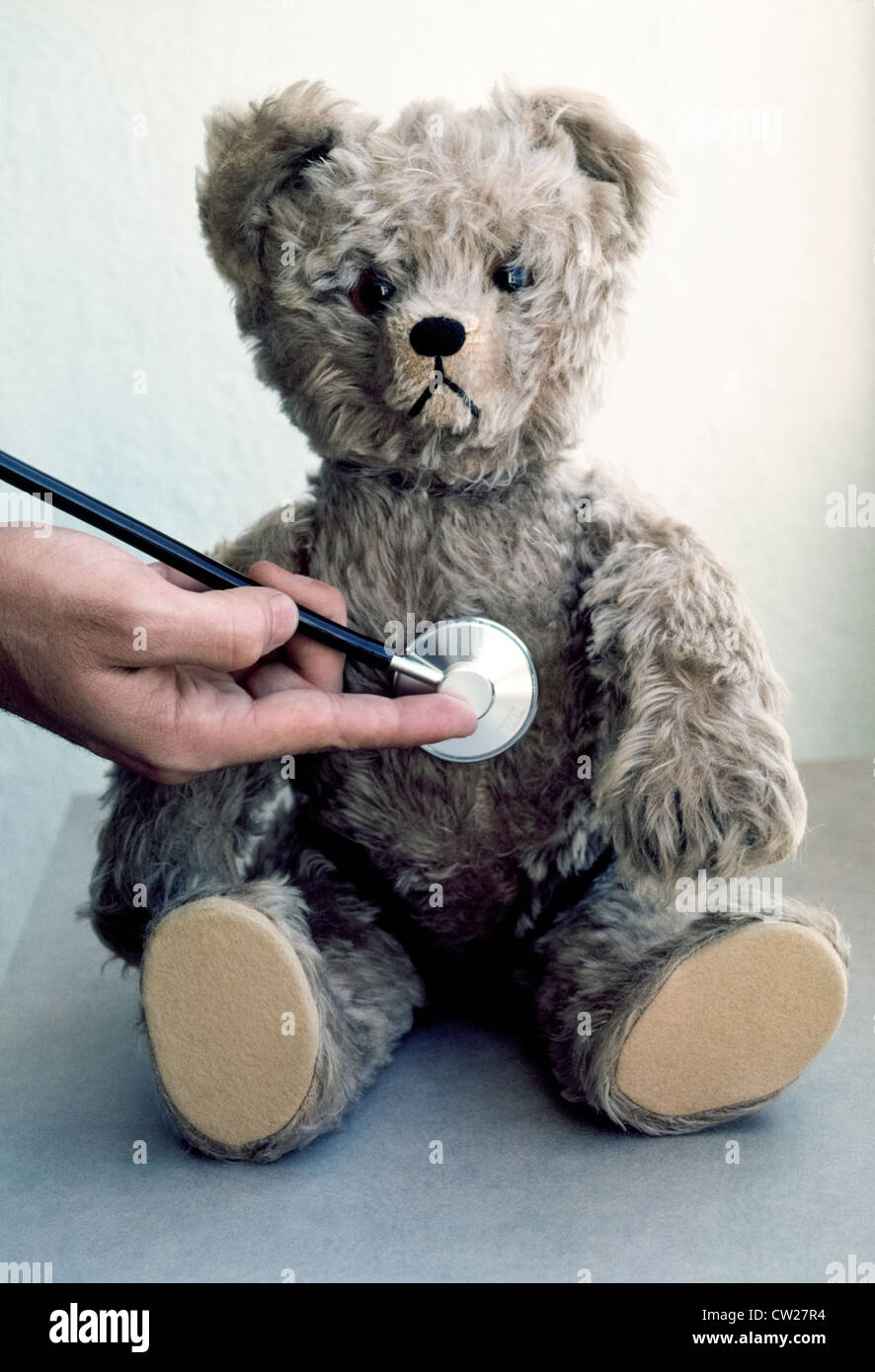 A medical stethoscope is used to check a toy Teddy Bear's heartbeat  to teach young children not to be afraid - Stock Image