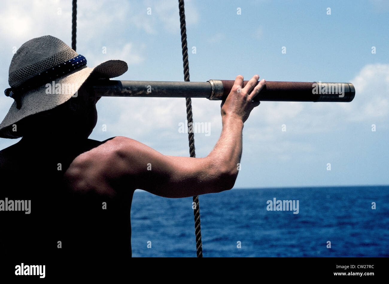 A young man with a long telescope is literally 'looking to the future' as he scans the sea from the deck - Stock Image