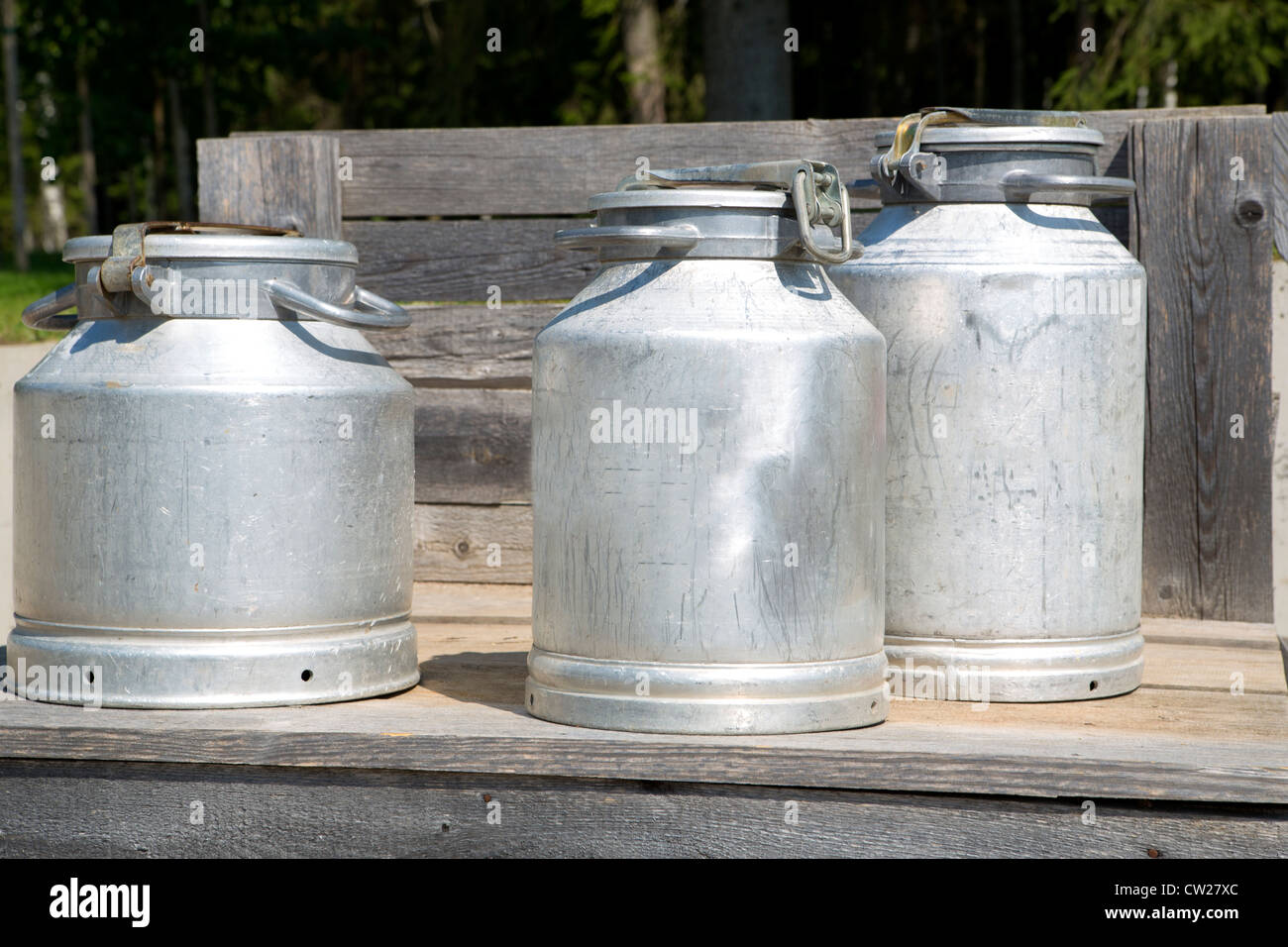 Three different sizes milk cans on scaffold - Stock Image