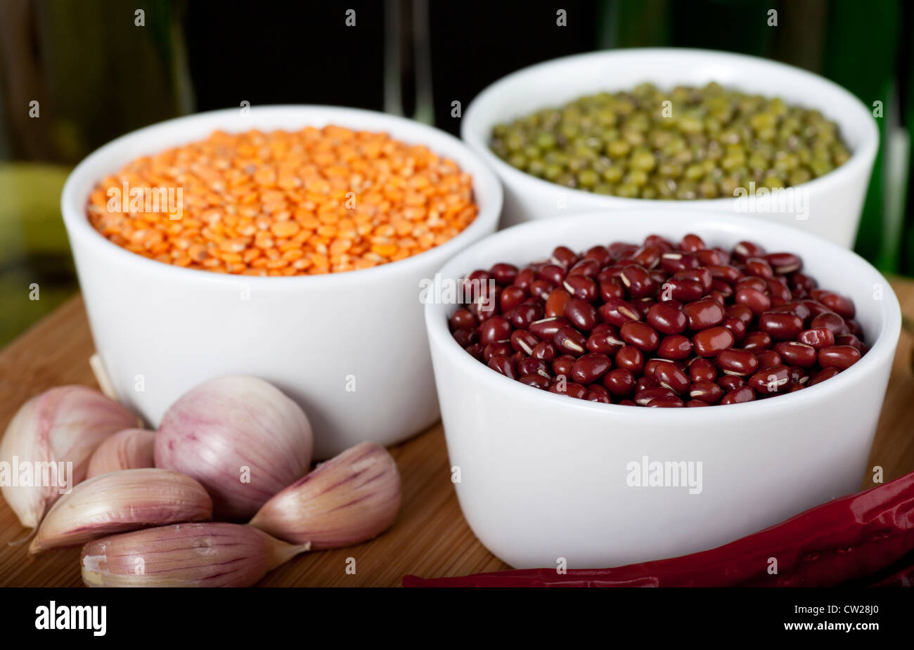 Three types of beans: lentils, mung and adzuki, with cloves of garlic. - Stock Image