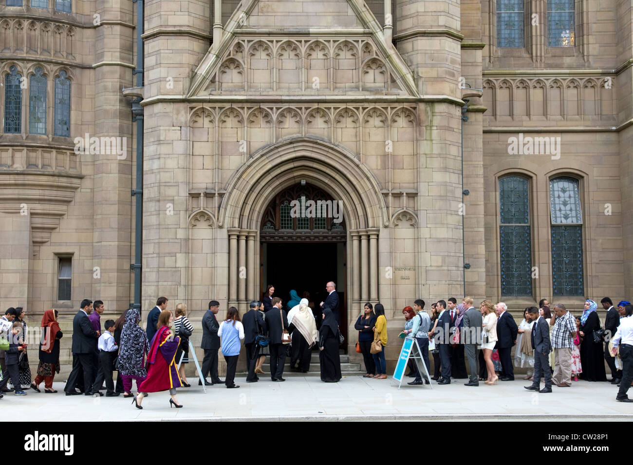 Families and guests queue for the Degree Ceremony, Whitworth Hall, University of Manchester, Manchester, England, - Stock Image