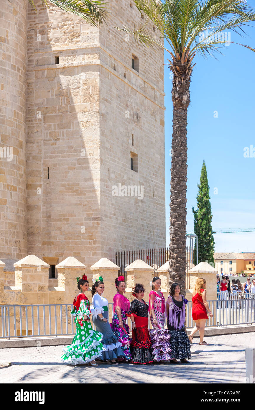Calahorra Tower in Cordoba Spain. Women posing dressed in traditional Spanish flamenco dresses for the May Feria - Stock Image