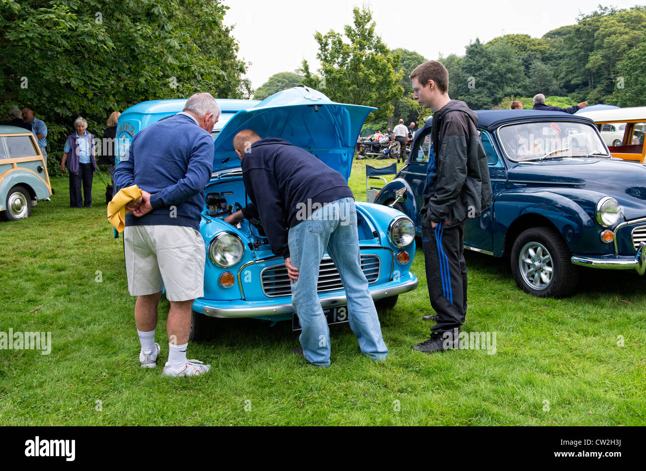 Classic Morris Minor motor car with enthusiasts at a classic car show at Lytham Hall in Lytham, Lancashire - Stock Image