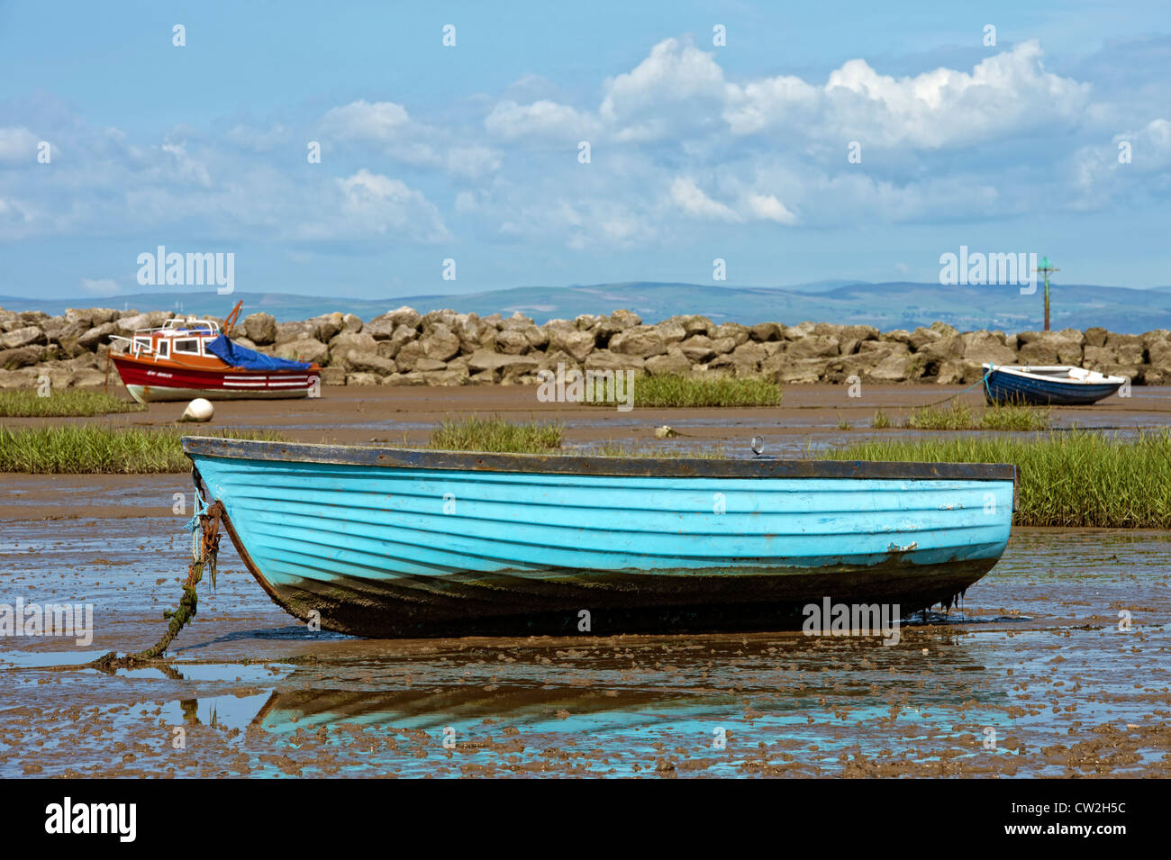 Old blue wooden rowing boat beached by the ebb tide in Morecambe Bay, Lancashire - Stock Image