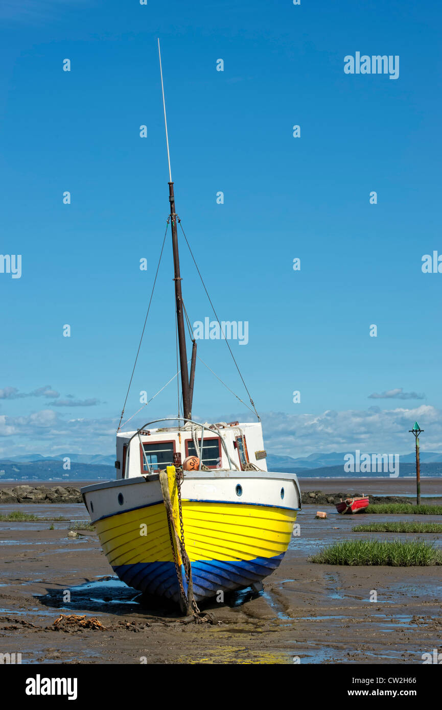 Yellow wooden fishing boat beached by the ebb tide in Morecambe Bay, Lancashire - Stock Image