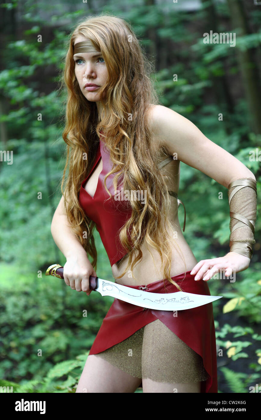 portrait of young woman with sword at forest - Stock Image