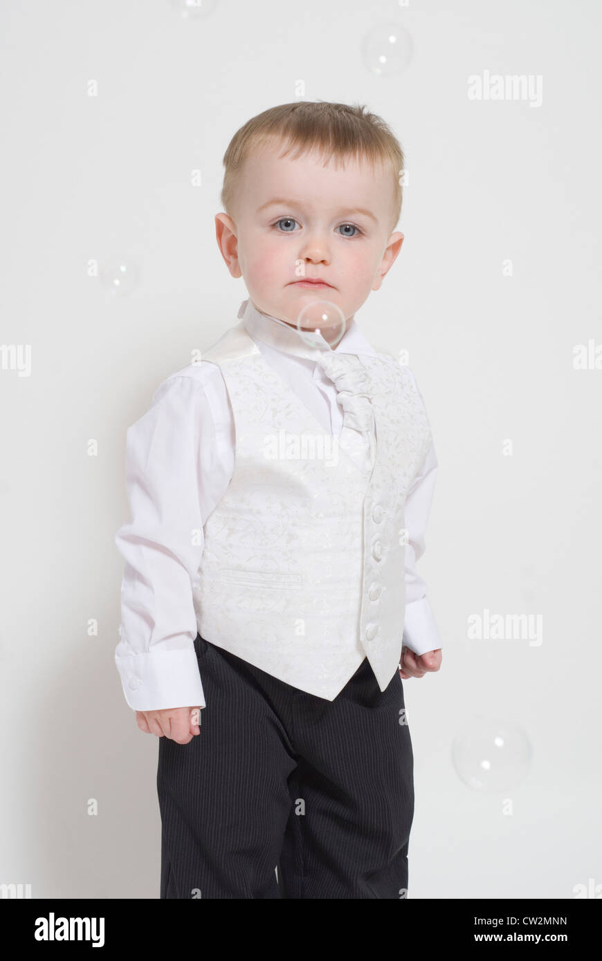 Little Boy, Toddler, Unamused by Bubbles, Dressed up in Smart Suit & Waistcoat, Studio Portrait Cut Out on White - Stock Image
