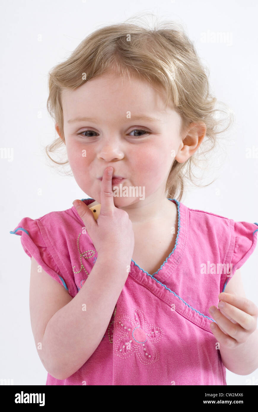 Sshhhhhh! Cute Little Girl Holding up finger to her mouth in Shushing Gesture, Studio Portrait Isolated on White Stock Photo