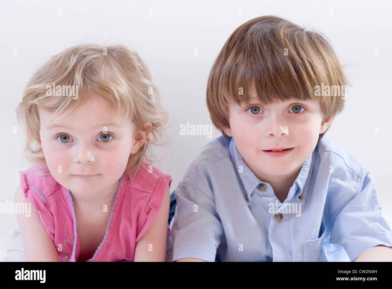 Young Boy and Baby Sister Lying on Their Tummies Side by Side Looking towards Camera, Studio Portrait Isolated on - Stock Image