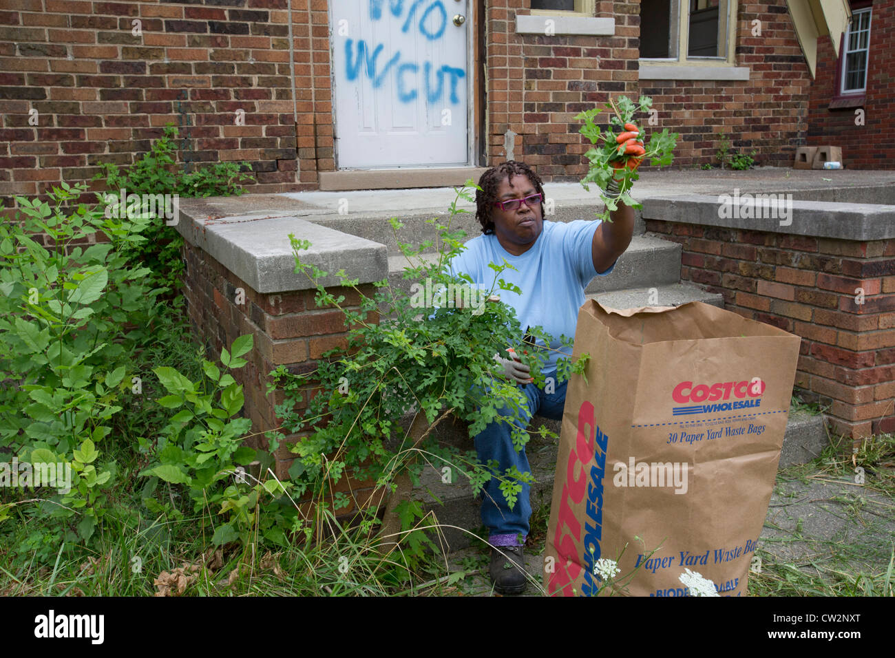 Detroit, Michigan - Members of the Three Mile Block Club cut weeds and remove illegally-dumped trash at an abandoned Stock Photo