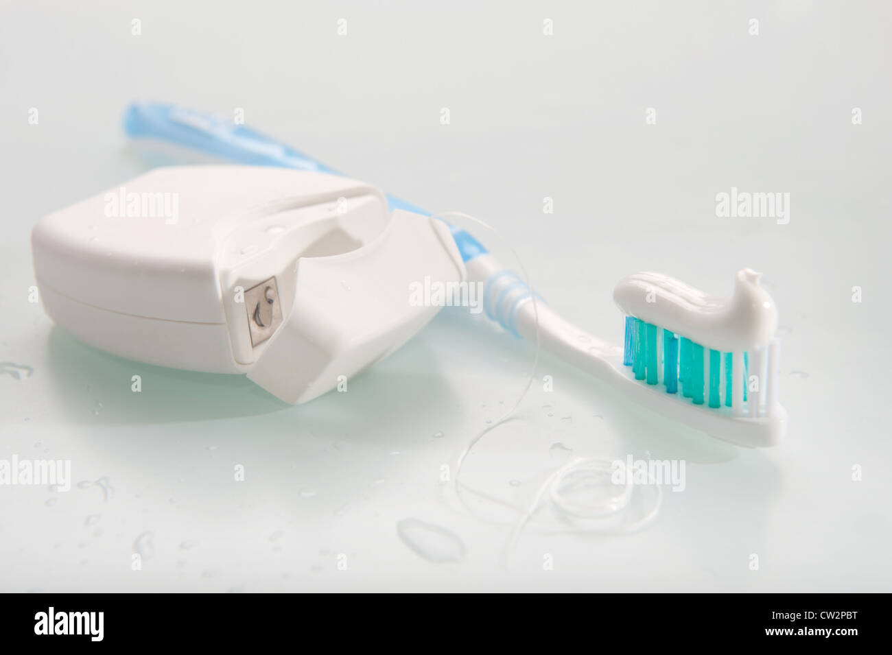 Toothbrush with toothpaste and dental floss on light background - Stock Image