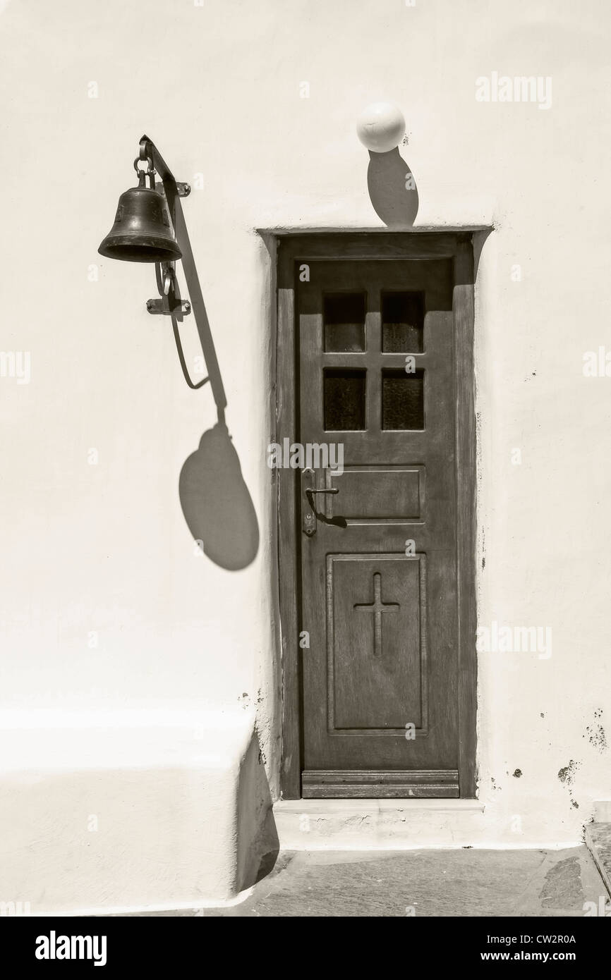 light and shadow - bell and lamp cast shadows next to a wooden door with a cross - Stock Image