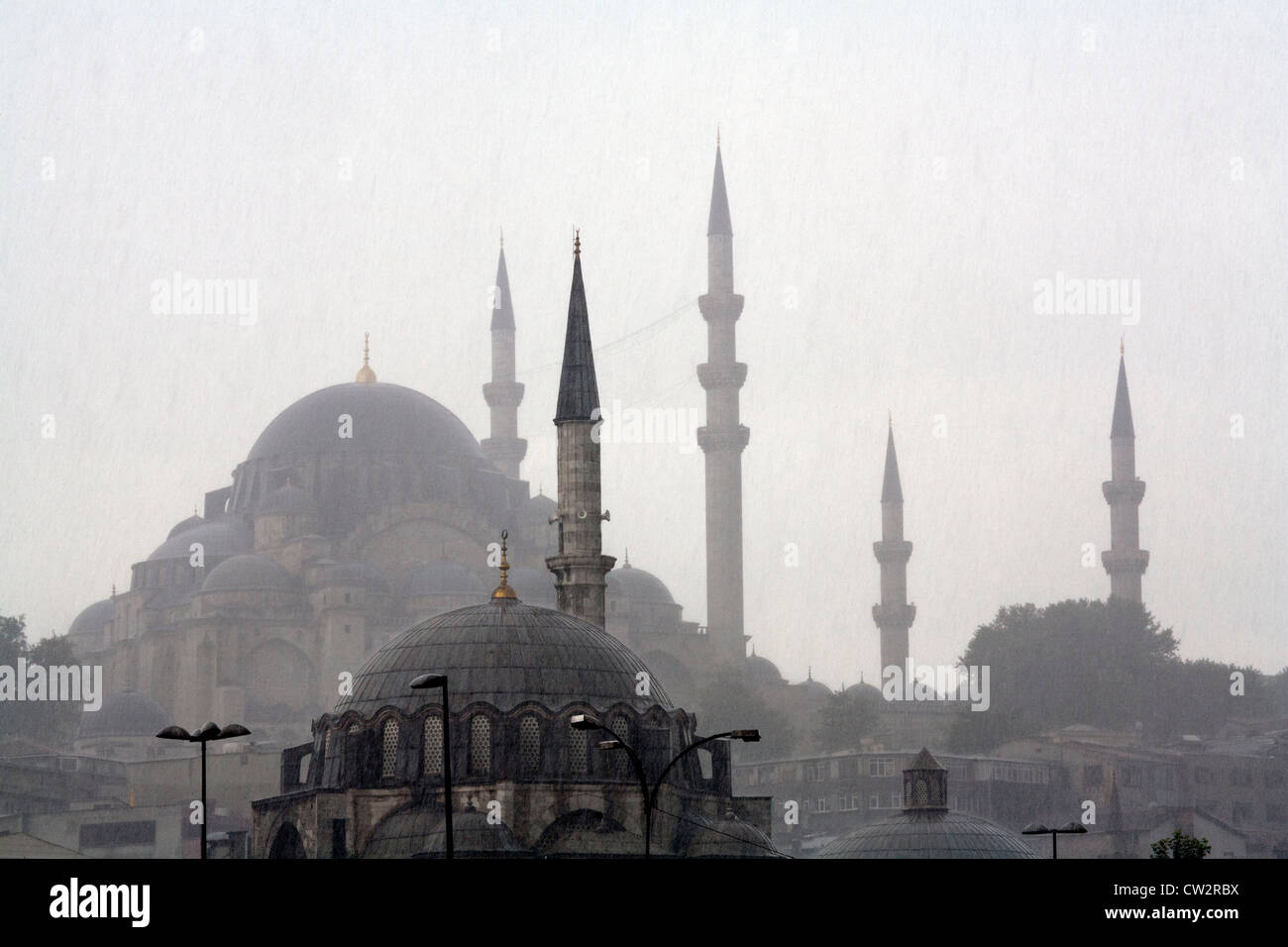 The top roofs domes of the new mosque Yeni camii Istanbul under heavy rein Turkey - Stock Image