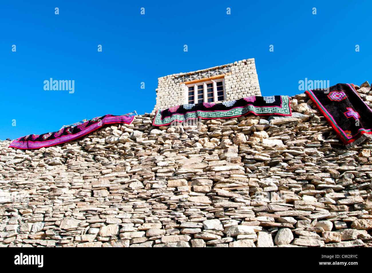 Three colorful patterned rugs hanging over a handmade stone wall with a house above in the village of Korzok, Ladakh, - Stock Image